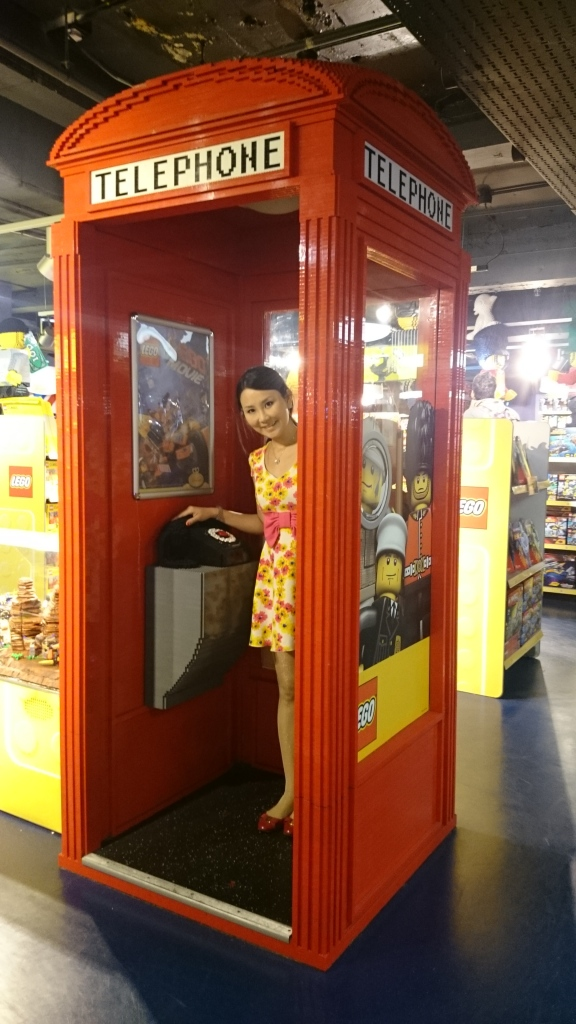 standing inside the famous red telephone booth made out of lego blocks